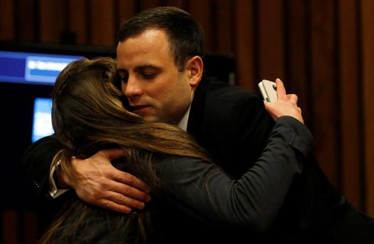South African Olympic and Paralympic sprinter Oscar Pistorius greets a well wisher during his murder trial in the North Gauteng High Court in Pretoria REUTERS/Mike Hutchings