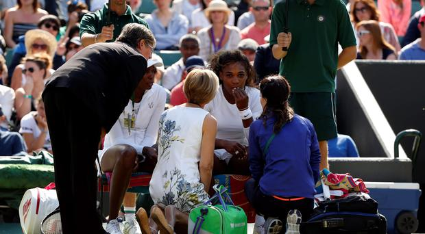 Serena Williams receives treatment alongside sister Venus Williams before their doubles match on day nine of Wimbledon