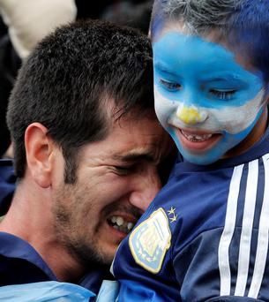 An Argentina fan reacts after an Argentine goal against Switzerland during their 2014 World Cup soccer match, at a public square viewing area in Buenos Aires July 1, 2014. REUTERS/Enrique Marcarian (ARGENTINA - Tags: SPORT SOCCER WORLD CUP)