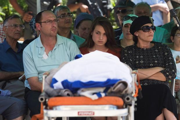 Bat-Galim (front R), Ofir (front L) and Shirel (front C) Shaer, parents and sister of Gil-Ad, 16, one of three Israeli teens who were abducted and killed in the occupied West Bank, sit next to the Israeli flag-covered body of Gil-Ad during a memorial service before his funeral in the West Bank Jewish settlement of Talmon July 1, 2014