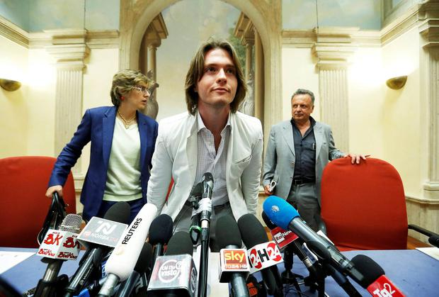 Raffaele Sollecito arrives at a news conference as he is flanked by his lawyers Giulia Bongiorno (L) and Luca Maori (R) in Rome