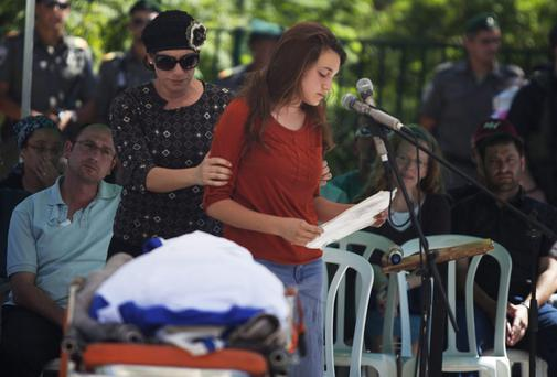 Bat-Galim Shaer, (C) supports her daughter Shirel Shaer as she speaks at the funeral ceremony of Gilad Shaer, 16, at his hometown in Talmon settelment, West Bank. The bodies of Eyal Yifrah, 19, Gilad Shaar, 16, and Naftali Fraenkel, 16, were found on Monday, north of the Palestinian town Halhul, just north of Hebron (Photo by Lior Mizrahi/Getty Images)