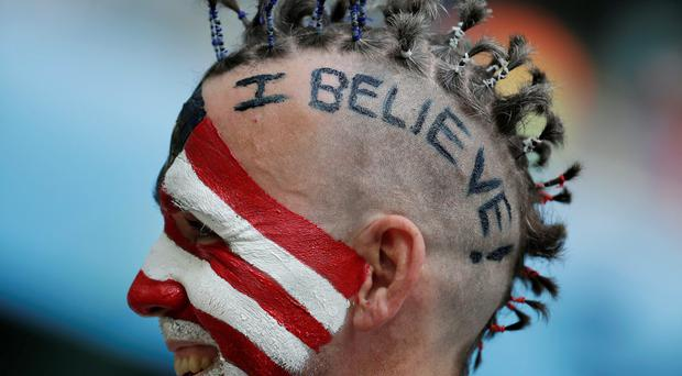 A US fan waits for the beginning of the World Cup round of 16 soccer match between Belgium and the USA at the Arena Fonte Nova in Salvador, Brazil