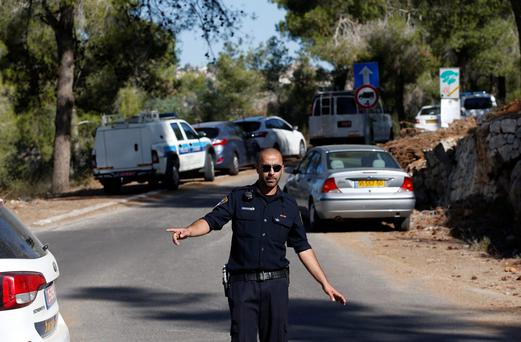 An Israeli police officer gestures in the Jerusalem Forest where a body was found