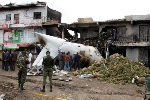 Soldiers and airport staff members look at the wreckage of the Fokker 50 cargo plane after it crashed shortly after takeoff at Kenyatta International Airport. (AP Photo/Khalil Senosi)