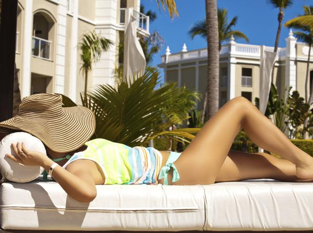 Vacation woman in hat relaxing on luxury white sunbed