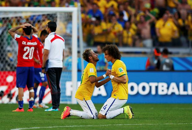 Brazil's David Luiz (R) and Neymar celebrate their win against Chile after their penalty shootout in their 2014 World Cup round of 16 game at the Mineirao stadium in Belo Horizonte