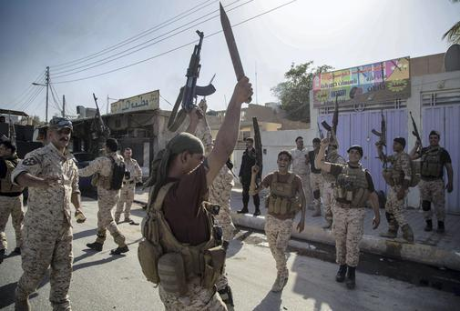 Iraqi security forces celebrate after clashes with followers of Shiite cleric Mahmoud al-Sarkhi, in front of his home in the Shiite holy city of Karbala, 50 miles (80 kilometers) south of Baghdad, Iraq. (AP Photo/Ahmed al-Husseini)