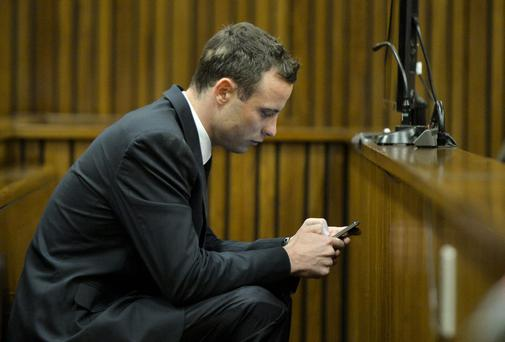 Oscar Pistorius checks his phone in the Pretoria High Court in Pretoria, South Africa. Photo credit: Herman Verwe/Foto24/Gallo Images - Pool/Getty Images