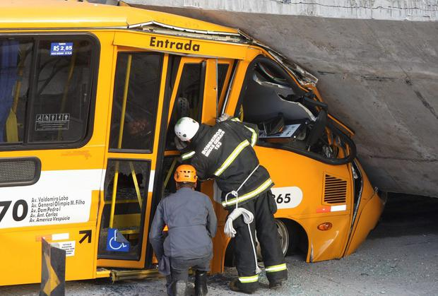 Rescue workers inspect a bus trapped underneath a bridge that collapsed while under construction in Belo Horizonte, July 3, 2014