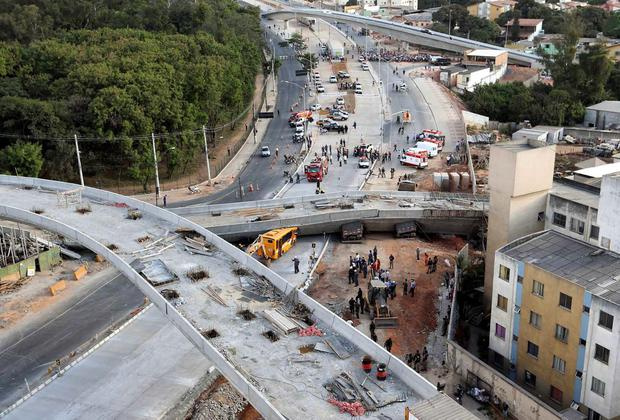 Rescue workers try to reach vehicles trapped underneath a bridge that collapsed while under construction in Belo Horizonte. REUTERS/Carlos Greco-DYN