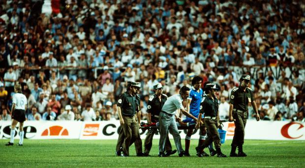 France's Patrick Battiston is carried off the field on a stretcher badly injured with a damaged vertebrae, a broken jaw and the loss of four of his front teeth after a contentious collision with West Germany goalkeeper Harald Schumacher. Photo: Steve Powell/Getty Images