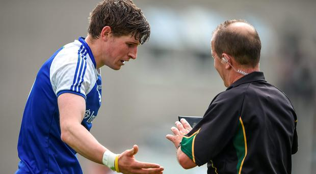 Monaghan's Darren Hughes pleads for leniency with referee Eddie Kinsella before black-carded against Tyrone. The card was later rescinded. Photo: Brendan Moran / SPORTSFILE