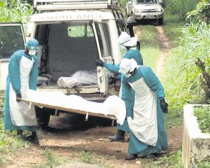 Health workers carry the body of an Ebola virus victim in Kenema, Sierra Leone, June 25, 2014. The Ebola outbreak has killed 467 people in Guinea, Liberia and Sierra Leone since February, making it the largest and deadliest ever, according to the World Health Organization (WHO). West African states lack the resources to battle the world's worst outbreak of Ebola and deep cultural suspicions about the disease remain a big obstacle to halting its spread, ministers said on Wednesday. Picture taken June 25, 2014. REUTERS/Umaru Fofana (SIERRA LEONE - Tags: HEALTH SOCIETY TPX IMAGES OF THE DAY)