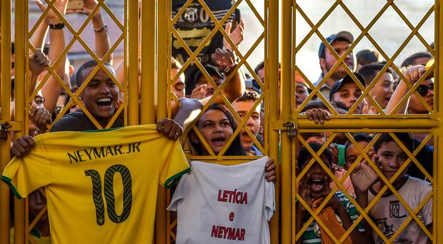 Brazilian football fans crowd outside the gate as their national team arrives for training session at the President Vargas stadium on the eve of the FIFA World Cup 2014 quarter-final match between Brazil and Colombia in Fortaleza
