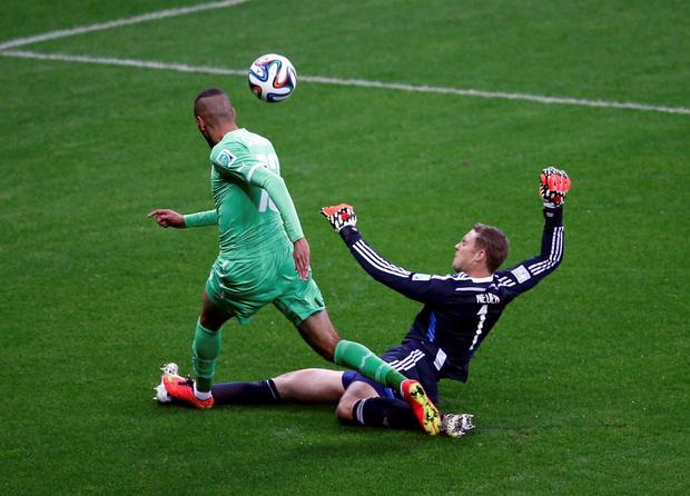 Germany's goalkeeper Manuel Neuer challenges Algeria's Islam Slimani during their 2014 World Cup round of 16 game at the Beira Rio stadium in Porto Alegre