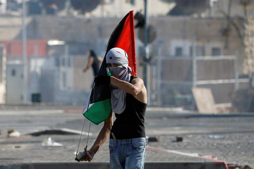 A Palestinian youth holds a Palestinian flag and and a sling during clashes with Israeli police after prayers on the first Friday of the holy month of Ramadan in Shuafat, an Arab suburb of Jerusalem. Reuters