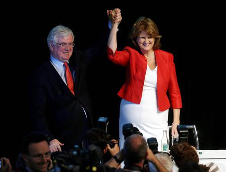New leader of the Labour party Joan Burton is congratulated by former leader Eamon Gilmore at the Mansion House in Dublin. PA