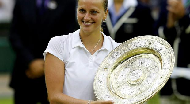 Petra Kvitova of the Czech Republic holds the winners trophy, the Venus Rosewater Dish, after defeating Eugenie Bouchard of Canada