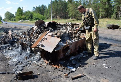 A member of the Ukrainian forces looks at a burned APC of pro-Russian militants, outside Nickolayevka, a small eastern Ukrainian city near Slavyansk