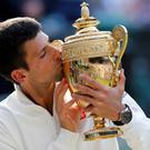 Novak Djokovic of Serbia kisses the winners trophy after defeating Roger Federer of Switzerland in their men's singles final tennis match at the Wimbledon Tennis Championships, in London July 6, 2014. Djokovic said that he dedicated his win to his former coach who died last year. REUTERS/Suzanne Plunkett