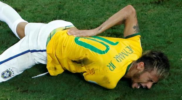 Brazil's Neymar grimaces in pain after a challenge by Colombia's Camilo Zuniga during their 2014 World Cup quarter-final match at the Castelao arena in Fortaleza
