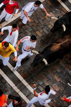 Revelers are chased by Dolores Aguirre's ranch fighting bulls during the running of the bulls of the San Fermin festival, in Pamplona, Spain, Tuesday, July 8, 2014