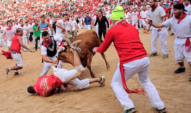 A reveler is hit by a cow on the bull ring, at the San Fermin festival, in Pamplona, Spain, Tuesday, July 8, 2014