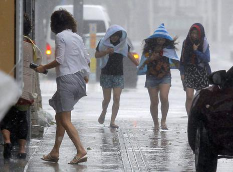 Women walk amid torrential weather in Okinawa yesterday. AP
