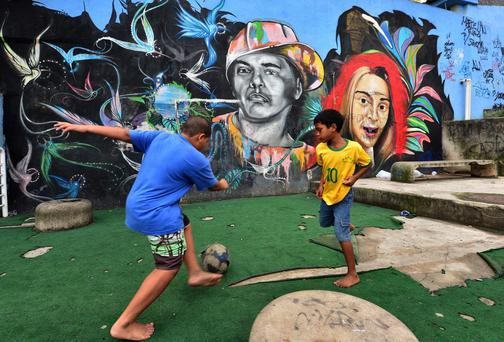 Children play football in Rocinha, Brazil's largest and most populous favela located in Rio de Janeiro. Photo: GIUSEPPE CACACE/AFP/Getty Images