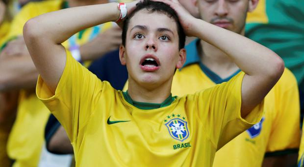 A fan of Brazil reacts during their 2014 World Cup semi-finals against Germany at the Mineirao stadium in Belo Horizonte