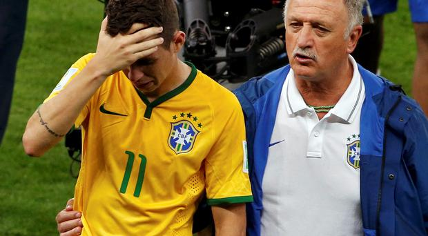 Brazil's Oscar (L) is comforted by coach Luiz Felipe Scolari after they lost their 2014 World Cup semi-finals against Germany at the Mineirao stadium in Belo Horizonte