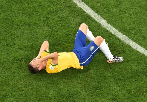 BELO HORIZONTE, BRAZIL - JULY 08: A dejected Oscar of Brazil lies on the pitch after being defeated by Germany 7-1 during the 2014 FIFA World Cup Brazil Semi Final match between Brazil and Germany at Estadio Mineirao on July 8, 2014 in Belo Horizonte, Brazil. (Photo by Francois Xavier Marit - Pool/Getty Images)