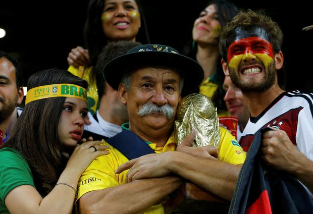 A Brazil fan (C) clutches a replica of the World Cup trophy as a Germany fan (R) celebrates after their 2014 World Cup semi-finals at the Mineirao stadium in Belo Horizonte July 8, 2014. REUTERS/Damir Sagolj