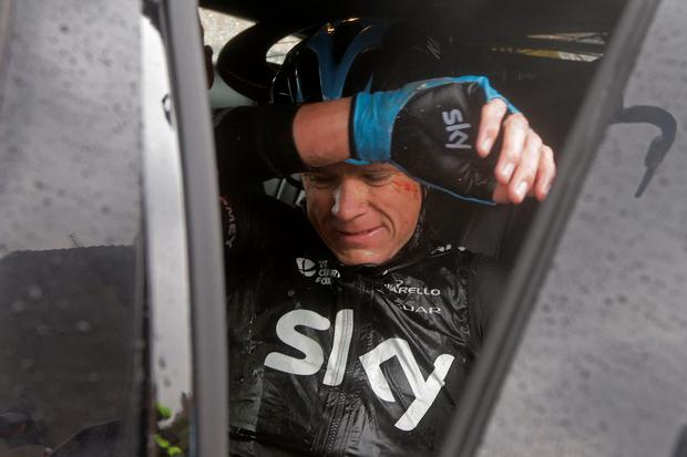 Chris Froome gets into his team car as he abandons the race following a third consecutive crash in two days during the fifth stage of the Tour de France