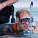 Britain's Prince William snorkels at a swimming pool, with British Sub-Aqua Club (BSAC) members, in central London. The Prince and his father Prince Charles attended a reception to mark the handover of the Presidency of BSAC from Prince Charles to Prince William. REUTERS/Justin Tallis/Pool