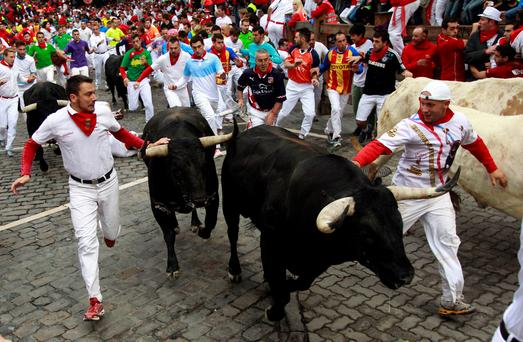 Runners sprint alongside Garcigrande fighting bulls at Telefonica Corner during the fourth running of the bulls of the San Fermin festival in Pamplona July 10, 2014. Two runners were gored in the run that lasted two and a half minutes, according to local media. REUTERS/Joseba Etxaburu