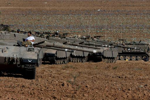 An Israeli soldier rests atop a tank stationed on a field outside the central Gaza Strip. Reuters