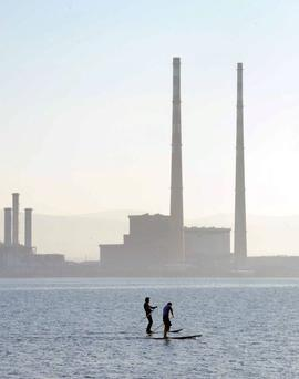 Two stand up paddle boarders pass the poolbeg towers in Dublin Harbour. Photo: Laura Hutton/ Photocall Ireland