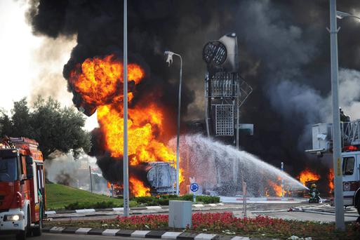 Israeli fire-fighters extinguish a fire that broke out after a rocket hit a petrol station in the southern Israeli city of Ashdod. Reuters