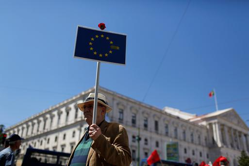 A demonstrator holds a banner near Portuguese parliament during a protest
