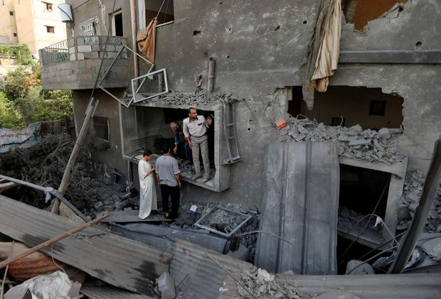 Palestinians survey a house which police said was damaged in an Israeli air strike on a neighbouring house in the northern Gaza Strip July 12, 2014