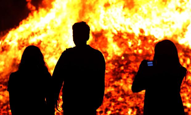 Members of the public take photographs at a bonfire on Sandy Row, Belfast on the eve of the annual 'Twelfth of July' celebrations, marking the victory of King William III's victory over James II at the Battle of the Boyne in 1690