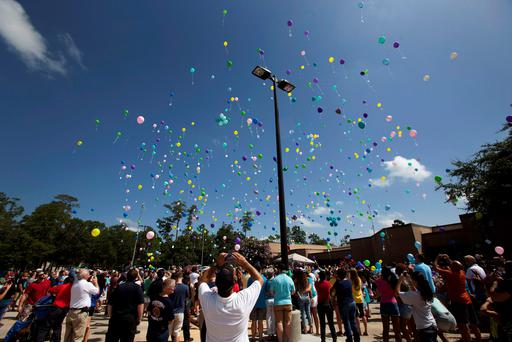Balloons are released during a memorial service for members of the Stay family who were murdered in their home Wednesday, in Spring, Texas