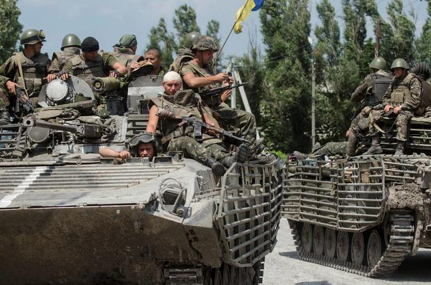 Ukrainian government soldiers drive atop their armored personal carriers outside the city of Siversk, Donetsk region, eastern Ukraine. Pro-Russian insurgents last week retreated from the strategic city of Slovyansk and holed up in Donetsk