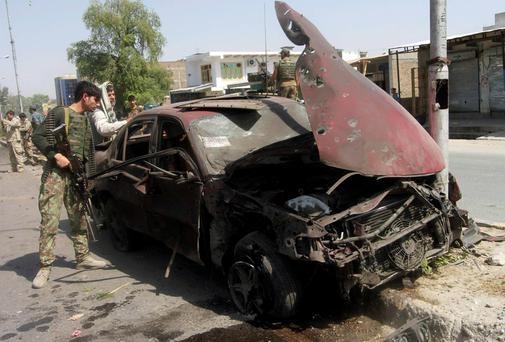 A member of the Afghan security force looks into a car, which was damaged after a blast in the eastern city of Jalalabad, in Nangarhar province