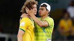Brazil's defender Thiago Silva (R) conforts Brazil's defender David Luiz after the semi-final football match between Brazil and Germany