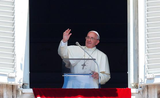Pope Francis waves during his Sunday Angelus prayer in Saint Peter's square
