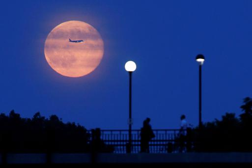 Aircraft passes in front of a Supermoon rising over the Rideau Canal in Ottawa, Canada