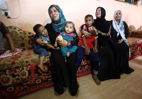 Relatives of four-year-old Palestinian boy Muayed al-Araj, who hospital officials said was killed in an Israeli air strike on his family's house, mourn during his funeral in Khan Younis in the southern Gaza Strip July 13, 2014. REUTERS/Ibraheem Abu Mustafa